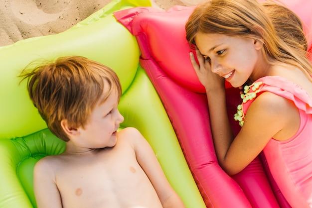 Kleine kinderen rusten op opgeblazen matrassen op het strand