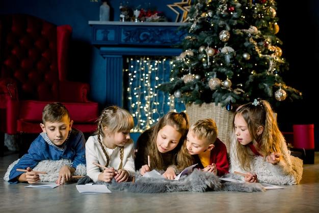Kleine kinderen schrijven de kerstman een brief op de achtergrond van een kerstboom