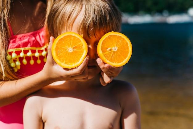Kleine kinderen spelen met oranje op het strand