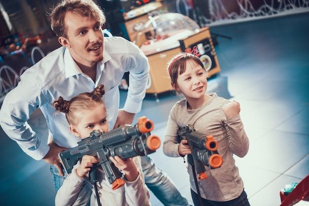 Kleine kinderen spelen schietspel met speelgoedgeweren