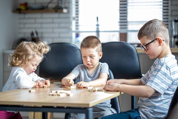 Kleine kinderen spelen thuis in de keuken een bordspel met houten blokjes.