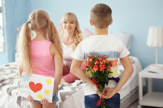 Kleine kinderen verstoppen cadeaus voor moeder achter hun rug thuis