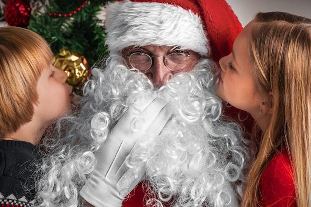 Kleine kinderen vertellen kerstwensen in het oor van de kerstman