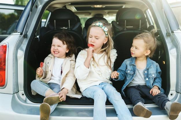 Kleine kinderen zitten in de kofferbak van een auto voor een roadtrip