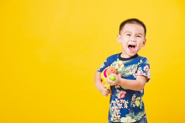 Kleine kinderenjongen in songkran-festivaldag die waterkanon houden