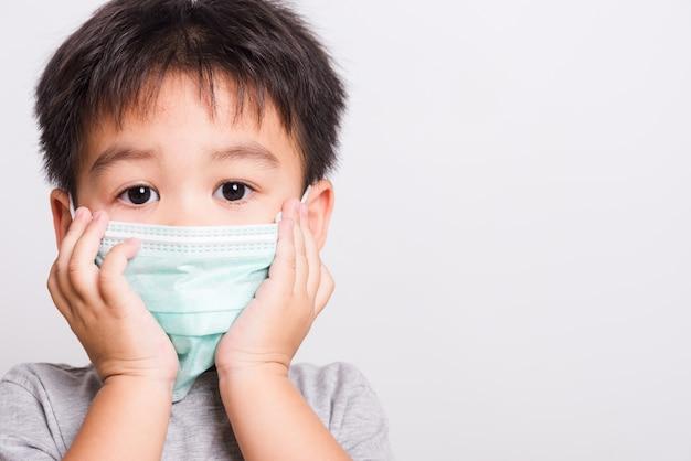 Kleine kinderenjongen ziek gebruikend gezondheidszorgmasker