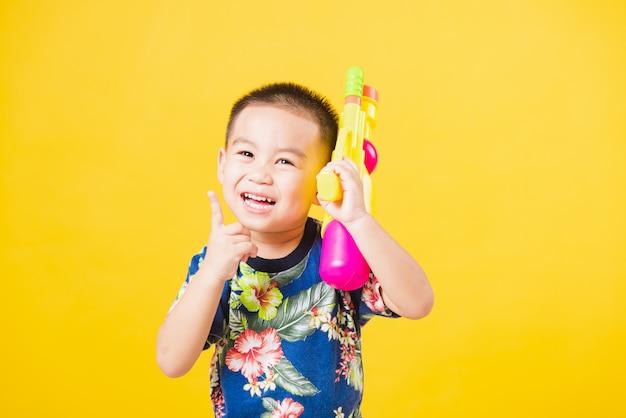 Kleine kinderenjongen zo gelukkig in songkran-festivaldag die waterkanon houden