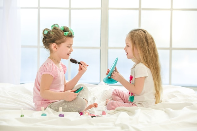 Kleine kindermeisjeszusjes die binnenshuis make-up doen
