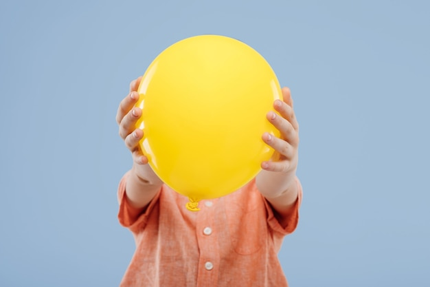 Kleine kindjongen die gezicht bedekt met gele ballon geïsoleerd op blauwe achtergrond kopie ruimte