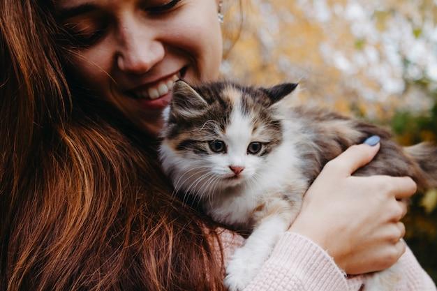 Kleine kitten zit op de handen van een vrouw