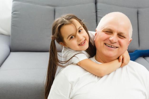 Kleine kleindochter knuffelen haar grootvader