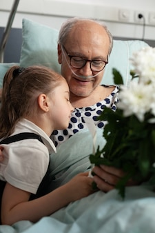 Kleine kleindochter knuffelt bejaarde grootvader die hem bezoekt in ziekenhuisafdeling