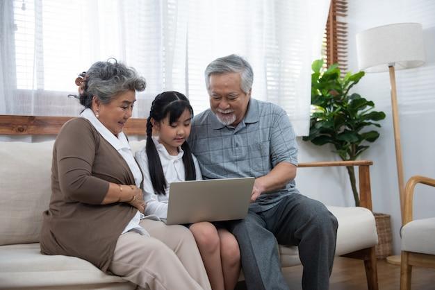 Kleine kleindochter leert senior oudere om te surfen op internet met behulp van computer en technologie en een moderne levensstijl.