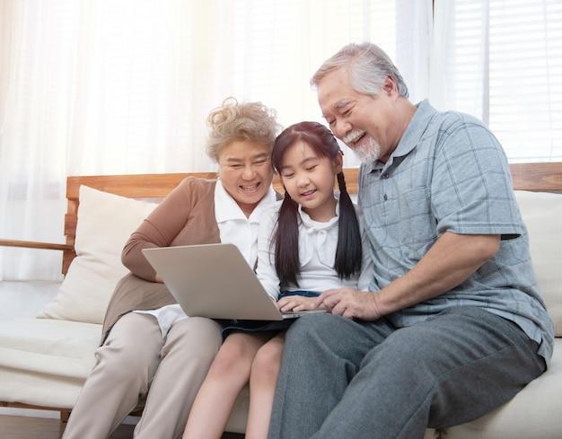 Kleine kleindochter leert senior oudere om te surfen op internet met behulp van computer