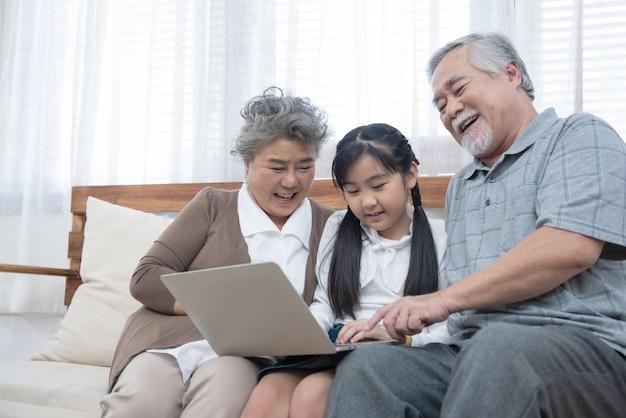 Kleine kleindochter leert senior ouderling om op internet te surfen met behulp van een computer moderne levensstijl.