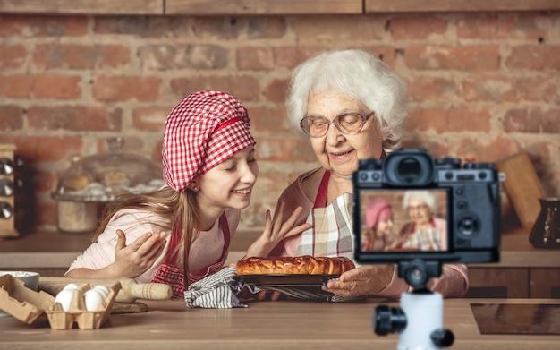 Kleine kleindochter met haar oudste oma die geniet van de geur van hete zelfgemaakte fruittaart