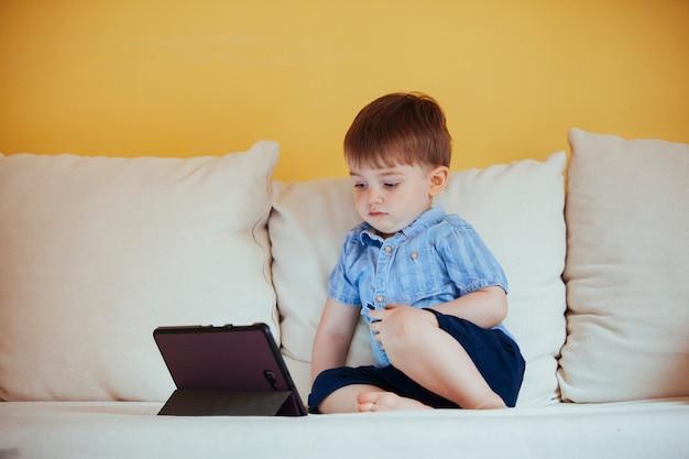 Kleine kleine babyjongen alleen kijken naar een scherm apparaat zonder oudercontrole thuis.