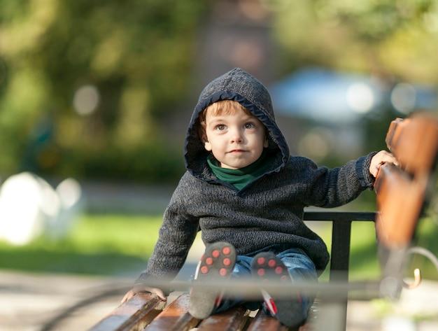 Kleine kleine jongen zittend op een bankje