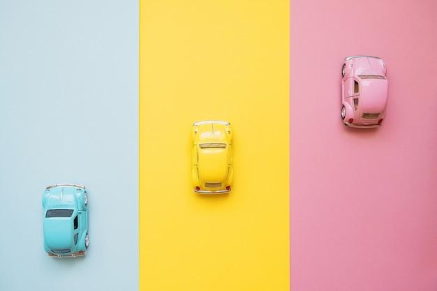 Kleine kleuren speelgoedauto's op een geel, roze en blauw. racen naar de finish
