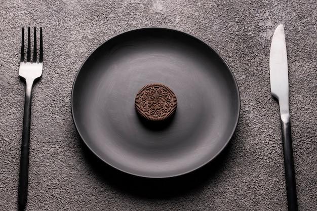 Kleine koekjes in een groot zwart bord, bestek, vork en lepel. een concept voor de inrichting van een restaurant, keuken of voor een artikel over dieet of desserts