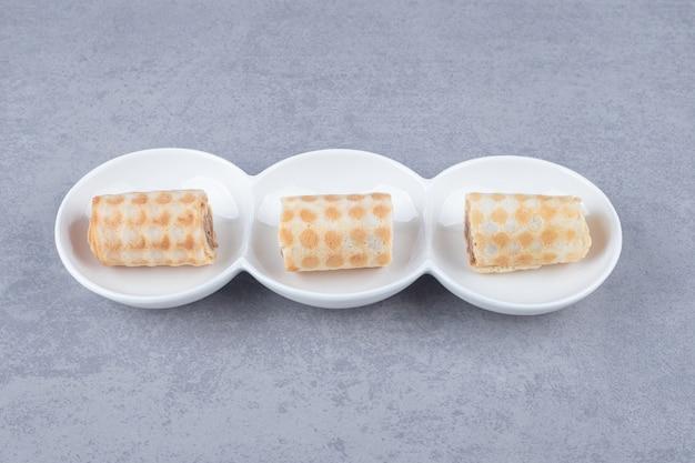 Kleine koekjes op een serveerschaal omringd met kaneelstokjes op marmer