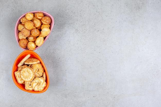 Kleine koekjes opgestapeld in twee kommen op een marmeren ondergrond