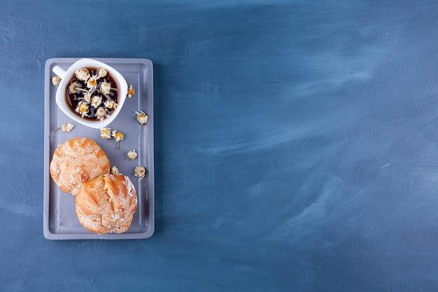 Kleine koekjes profitroles met suikerpoeder en kaneelstokjes.