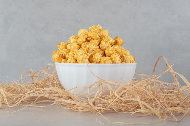 Kleine kom genesteld in een stapel rietjes, gevuld met caramel gecoate popcorn op marmeren tafel.