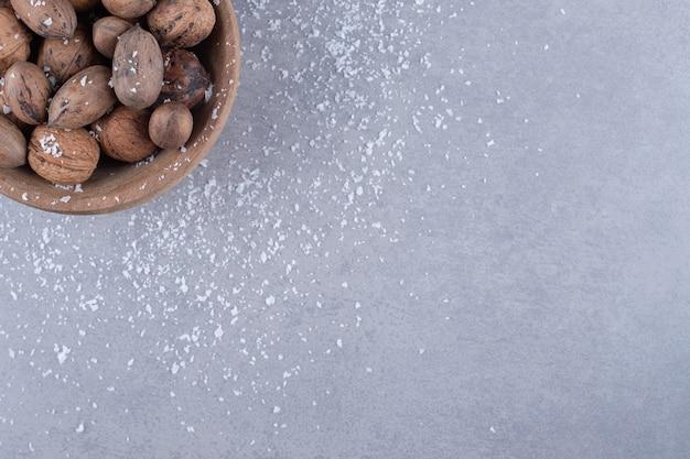 Kleine kom met diverse noten op marmeren oppervlak