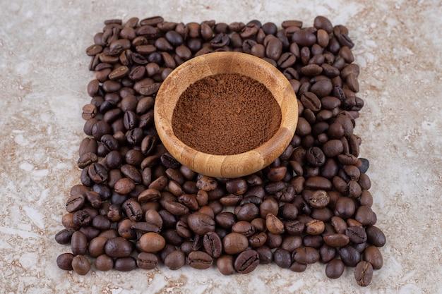 Kleine kom met koffiepoeder omringd met een kleine stapel koffiebonen