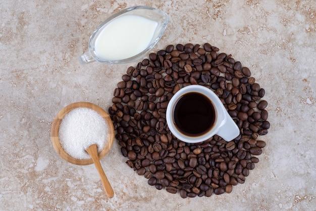 Kleine kom met suiker naast een stapel koffiebonen rond een kopje koffie