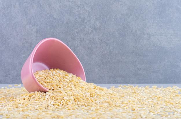 Kleine kom omgevallen op een verspreide massa bruine rijst op een marmeren oppervlak