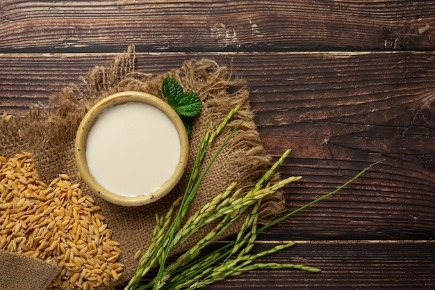 Kleine kom rijstmelk met rijstplnt en rijstzaad op houten vloer