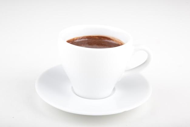Kleine kop warme chocolademelk op een wit bord in een witte kop