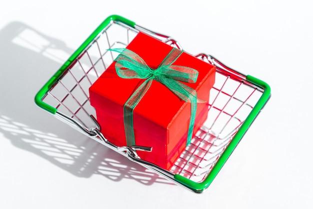 Kleine kruidenierswinkel mand met rode geschenkdoos op wit