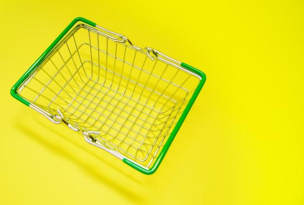 Kleine kruidenierswinkel metalen supermarkt winkelmandje. detailhandel consumentenaankopen online. levering van goederen bij u thuis. ruimte voor de tekst.