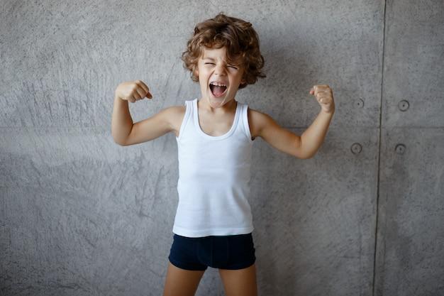 Kleine krullend schattig moedige jongen, vuisten omhoog te houden en biceps op betonnen grijze achtergrond te tonen.