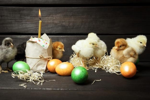 Kleine kuikens pasen cake en gekleurde eieren op een donkere houten tafel