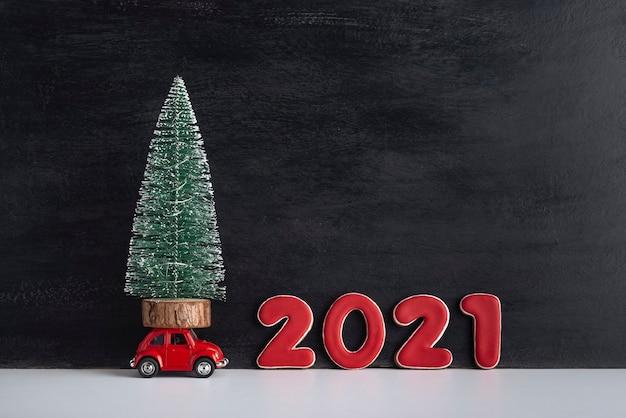 Kleine kunstboom op automodel naast het bord 2021. auto als cadeau. auto onder de boom.