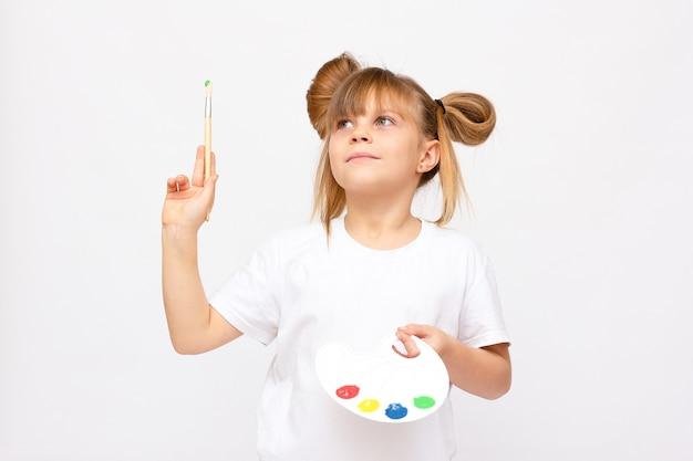 Kleine kunstenaar. aanbiddelijk meisje met waterverf het schilderen en palet, dat op witte achtergrond wordt geïsoleerd