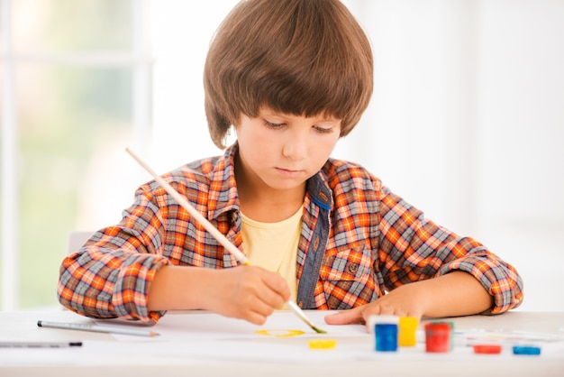 Kleine kunstenaar. geconcentreerde kleine jongen die ontspant tijdens het schilderen met aquarellen aan tafel