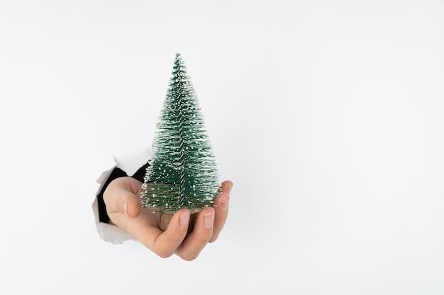 Kleine kunstkerstboom aan de hand in de palm van je hand staat een groene boom