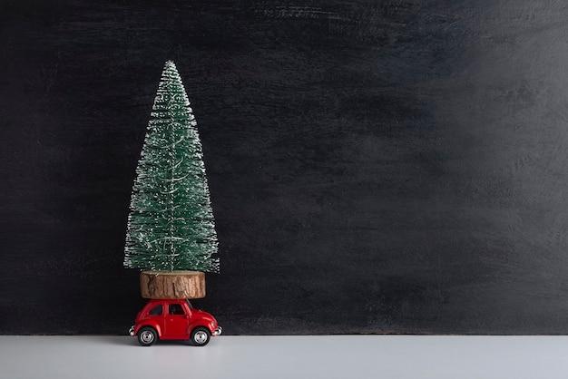 Kleine kunstmatige boom op dak van speelgoedauto op zwarte achtergrond. levering van kerstbomen. kopieer ruimte.