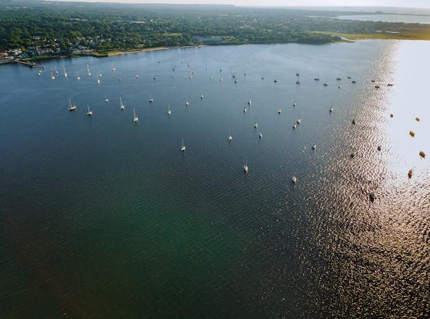 Kleine kustplaats in gebiedsmening van heuvel aan overzeese baaipier met jachtboten op water in de zomerdag