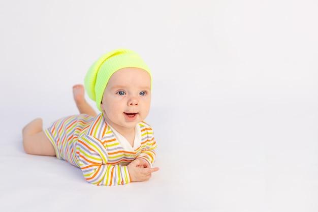 Kleine lachende babymeisje 6 maanden oud ligt in een lichte romper en gele hoed,