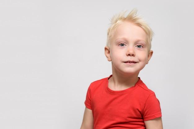 Kleine lachende blonde jongen in rode t-shirt. portret