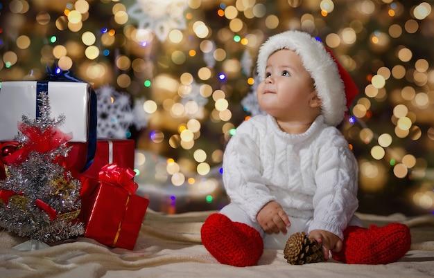 Kleine lachende jongen (baby) in een witte gebreide trui en muts van de kerstman op een oppervlak van kerstmisslinger en geschenkdozen met lint.