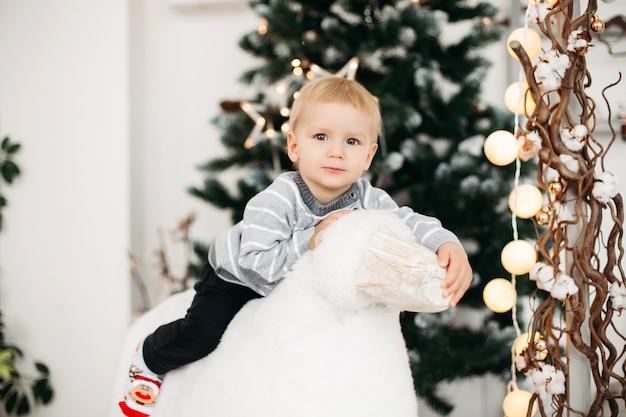 Kleine lachende jongen in grijze trui, zwarte spijkerbroek en schattige sokken zittend op wit groot stuk speelgoed, knuffelen het en kijken naar de voorkant
