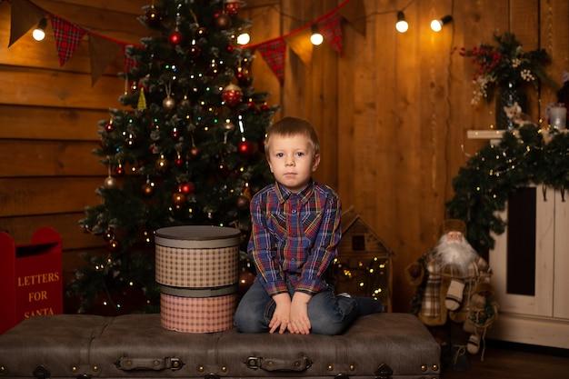 Kleine lachende jongen met kerst geschenkdozen in zijn handen