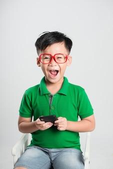 Kleine lachende kind jongen spelen of surfen op internet op digitale smartphone